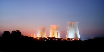 far off shot of a nuclear power plant after sunset